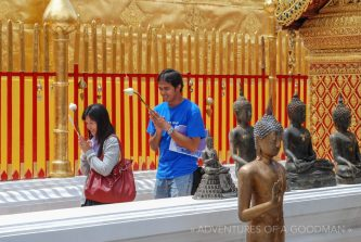 Locals walk around a temple while praying at Doi Suthep in Chiang Mai, Thailand