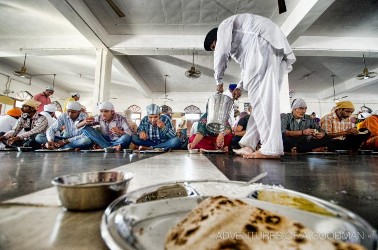 A man drops daal into the plates of hundreds of pilgrims at the Golden Temple Free Kitchen