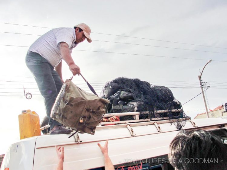 Our original driver removes bags from the roof of our microbus