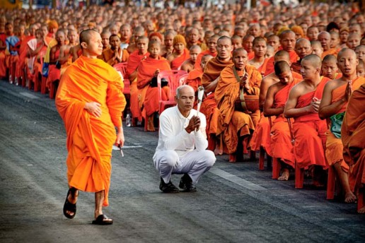 A devotee is surrounded by 12,999 monks in Chiang Mai, Thailand