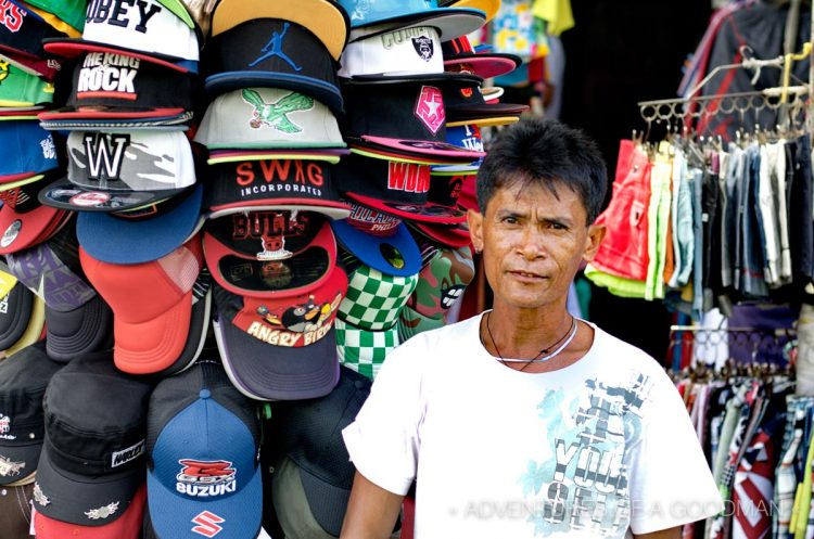 He kinda forgot to smile -- a baseball cap vendor at the Baclaran Market - Manila, Philippines