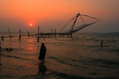 A local woman enjoys the sunset alongside Chinese fishing nets in Kerala, India
