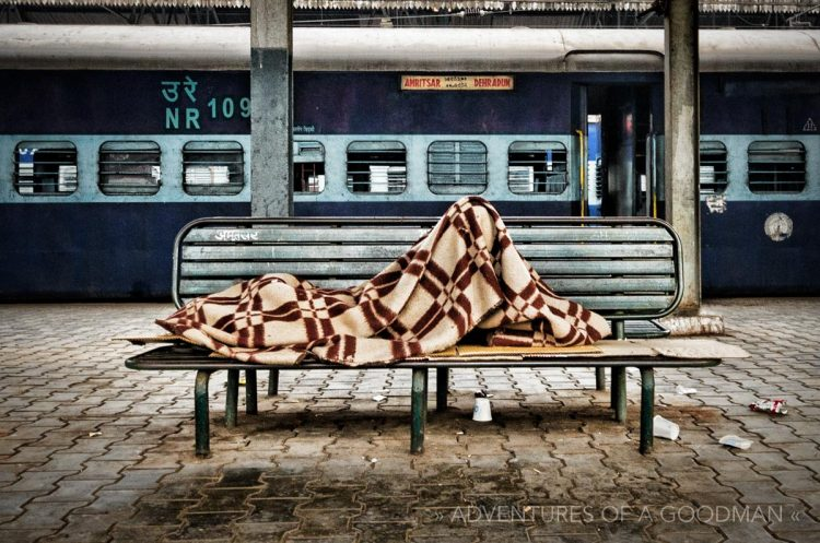 A sleeping passenger waits for his train in the main station in Amritsar, India