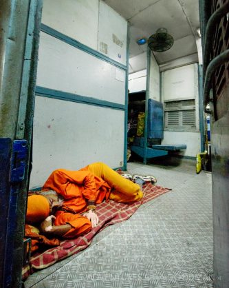 A Sadhu sleeping in the doorway of a Indian Overnight Train, stopped in the Haridwar train station