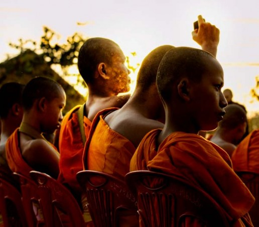A monk gets the energy of a camera at sunrise - 12,999 monk alms procession in Chiang Mai, Thailand