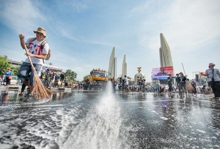Huge trucks of water sprayed down the street in front of the Democracy Monument in Bangkok