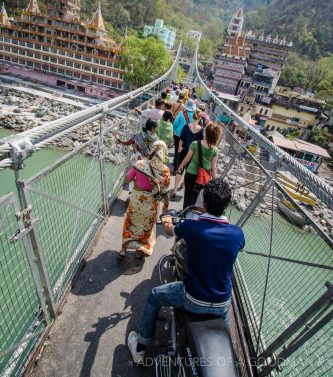 Tourists, motorcycles, locals, cows and monkeys cross the Laxshman Jhula Bridge in Rishikesh, India