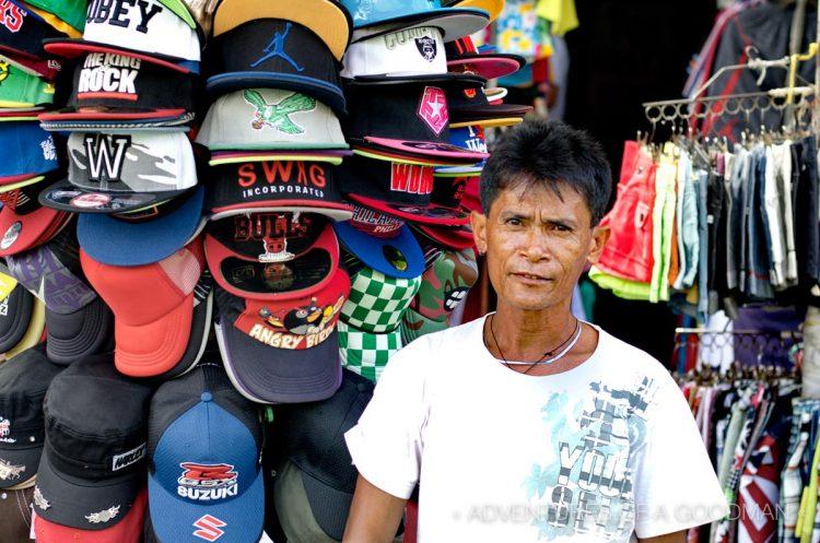 He kinda forgot to smile -- a baseball cap vendor at the Baclaran Market - Manila, Philippines