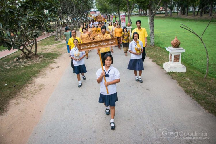 Local students march in a parade to celebrate the 86th birthday of King Bhumibol Adulyadej