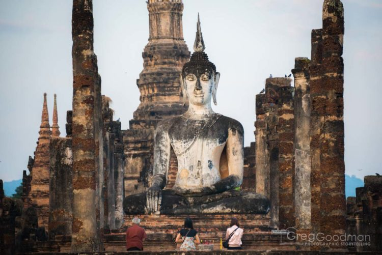 Early morning prayers in front of the giant Buddha statue at Wat Mahathat in Sukhothai